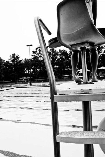 lifeguard sitting in a guard chair watching the pool