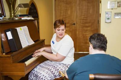 Music Therapist playing piano with resident.jpg