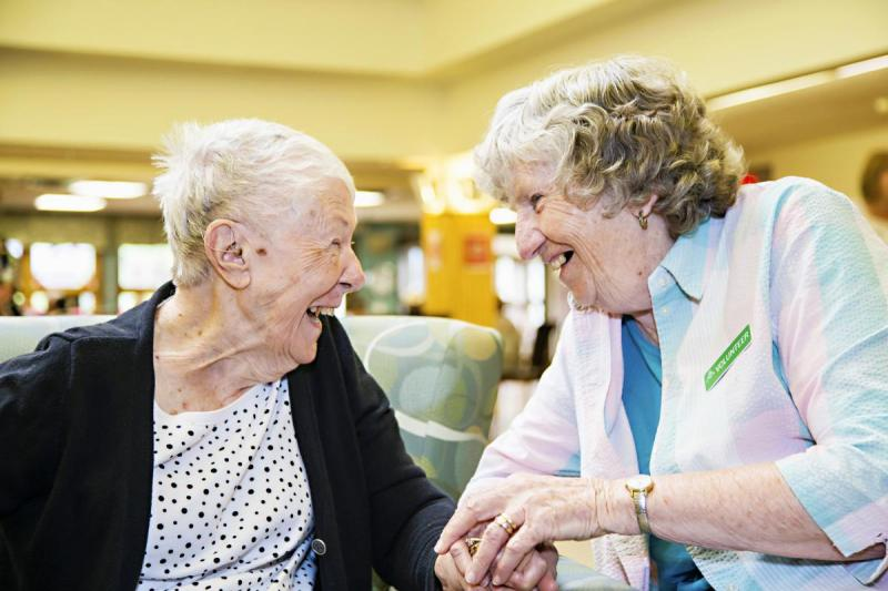 Volunteer and resident sitting holding hands, and laughing together