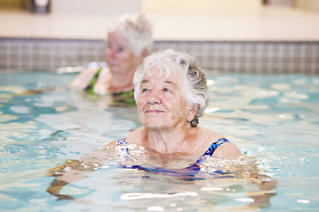 Happy resident smiling while in the pool for a resident swim