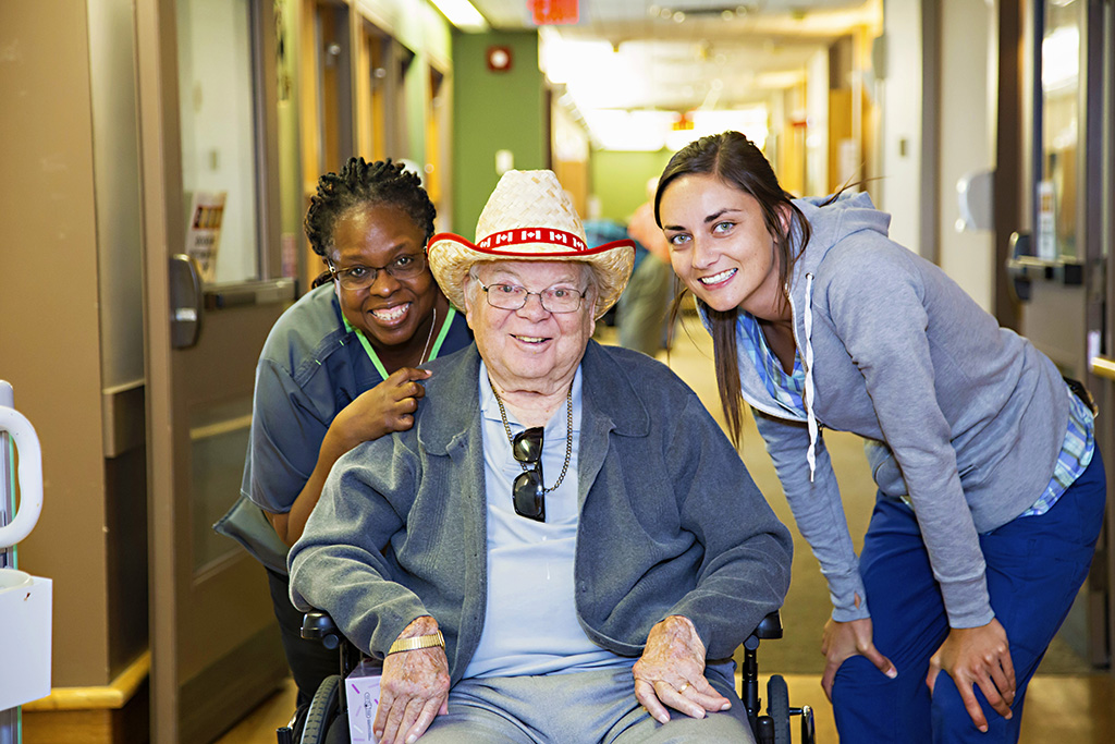 Two nursing staff membes with a male resident in a wheelchair