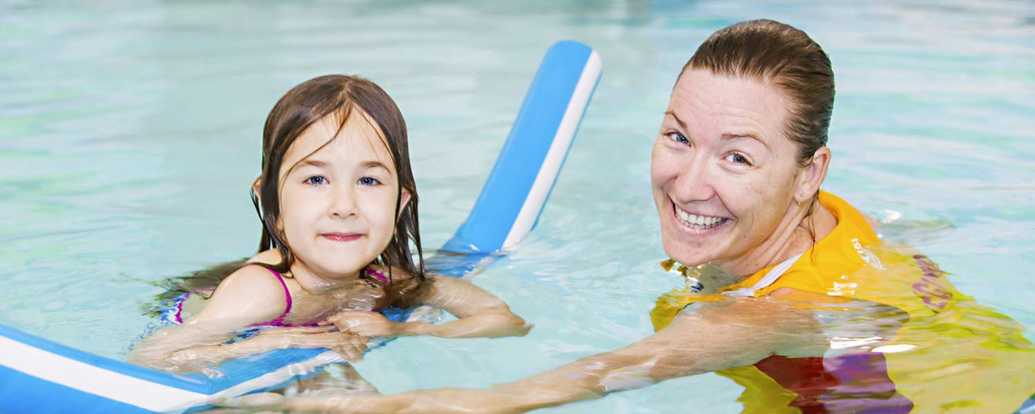 Child swimming with pool coordinator
