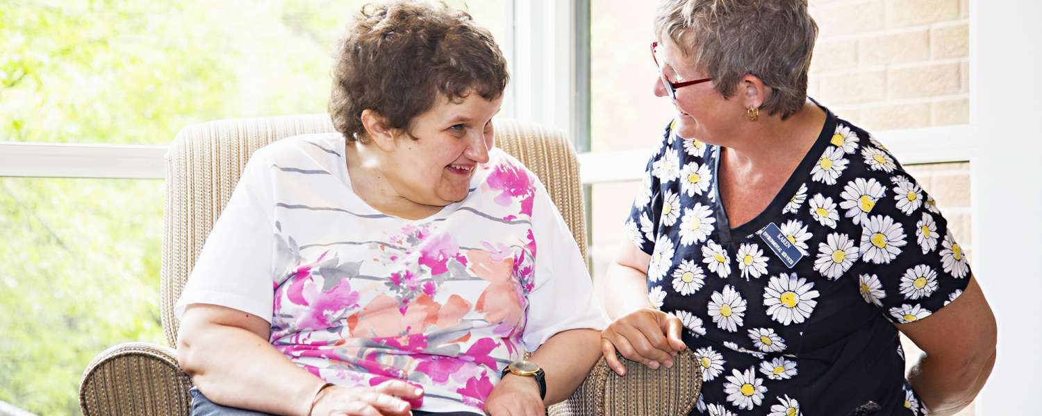 Female Resident and Staff Worker laughing in the Towers Lobby