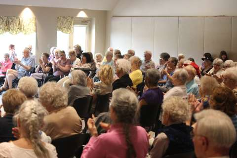 Happy Residents Clapping Hands in a Large Group