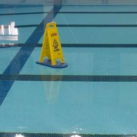 A picture of a Wet Floor sign floating on a fullterboard along the surface of a pool.