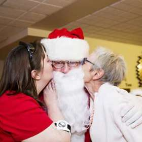 A resident and her daughter kissing Santa on the cheek