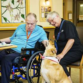 Male resident and volunteer enjoying pet therapy program
