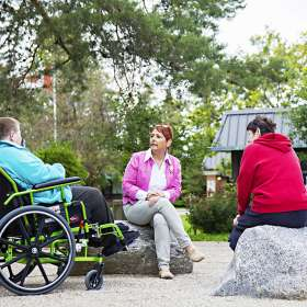 Two residents and Spiritual Care Coordinator enjoying conversation outdoors