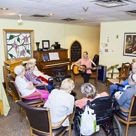 Group of residents enjoying musical therapy program in the chapel