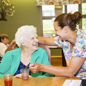 Female resident and PSW laughing in the dining room together