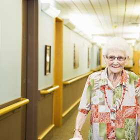 Female resident walking in hallway with a big smile
